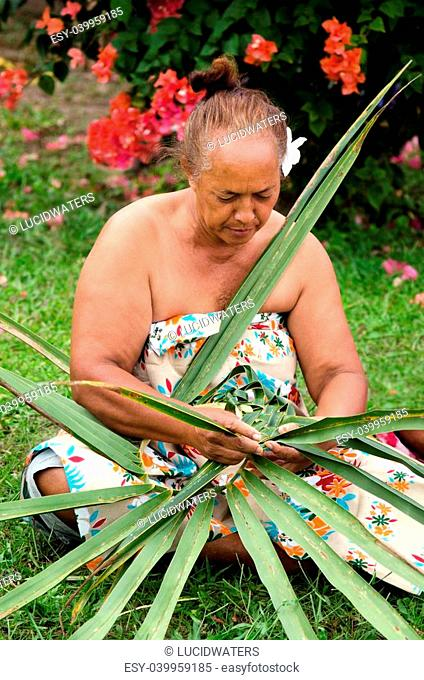 Portrait of Polynesian Pacific Island Tahitian mature female weaving a hat knees out of palm leaves outside her home in Aitutaki lagoon Cook Islands