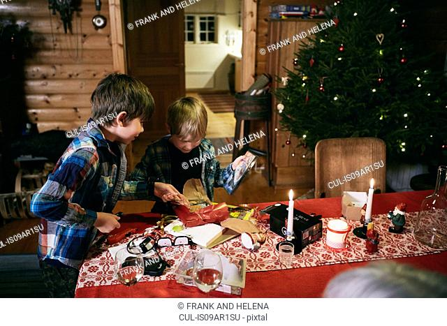 Two brothers opening Christmas presents at table