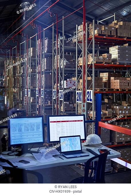 Desk with laptop and computers in distribution warehouse