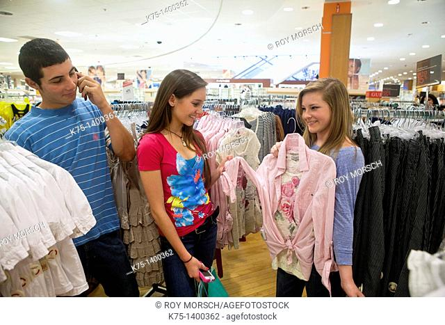 Girls shop while boy talks on cell phone