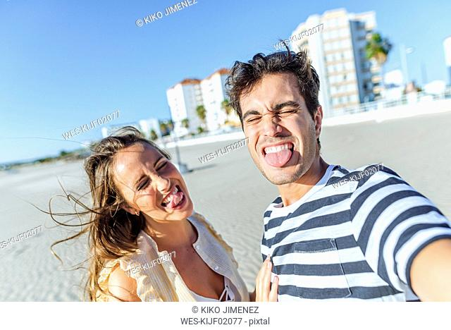 Funny selfie of a happy young couple on the beach