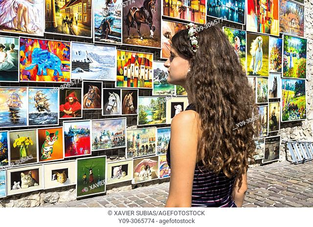 Girl looking at the paintings exhibited in the Medieval Fortification, Krakow, Poland