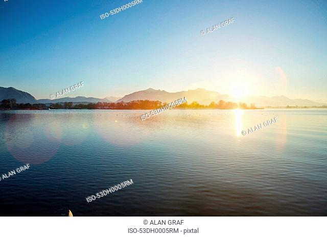 Mountains and sun over still rural lake