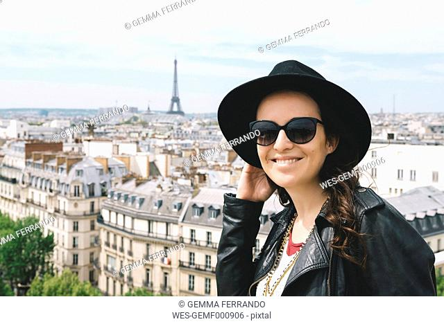 France, Paris, portrait of happy woman at viewpoint wearing a black hat and sunglasses