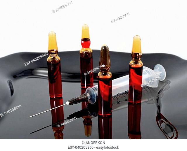 Four ampoules and syringe isolated on a black plate