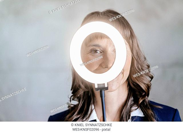 Businesswoman looking through ring of light