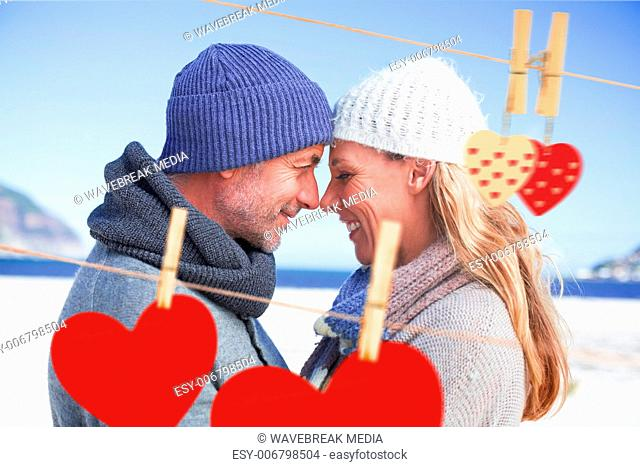 Composite image of attractive couple smiling at each other on the beach in warm clothing