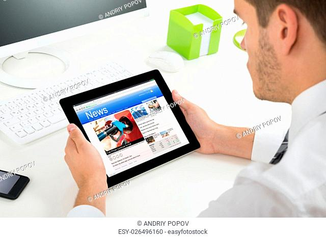 Close-up Of Businessman Videoconferencing With Colleagues On Digital Tablet At Desk