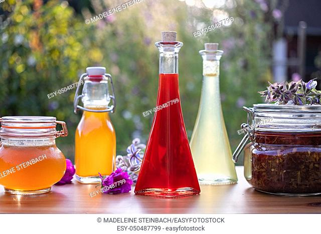 Homemade oil made from St. John's wort flowers, with various herbal syrups and flowers in the background