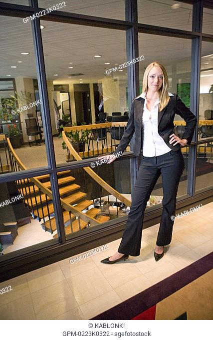 Portrait of young confident businesswoman standing by window in office