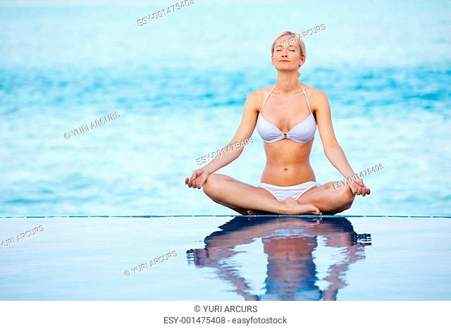 Portrait of fitness young woman meditating in lotus position at poolside