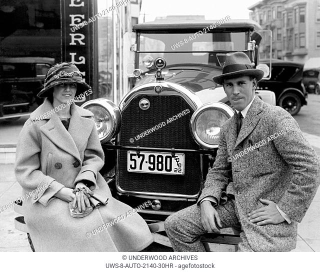San Francisco, California: c. 1922 A couple in front of the Peerless dealership sitting on the bumper of their 1922 Peerless that has Colorado plates