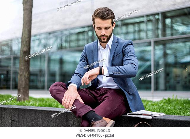 Young businessman sitting outdoors checking the time