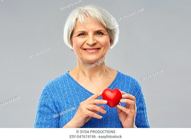 smiling senior woman with red heart