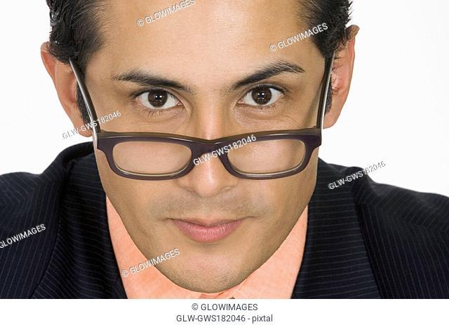 Portrait of a businessman peeking over his eyeglasses