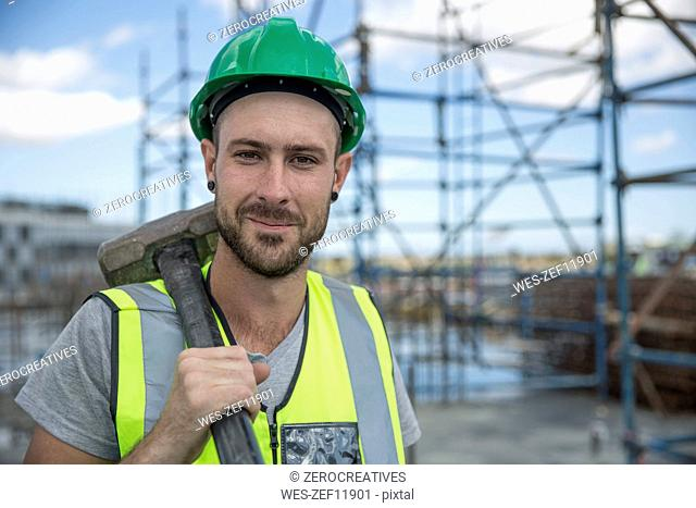 Construction worker on construction site holding sledge hammer