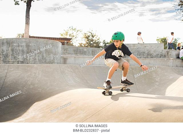 Mixed Race boy skateboarding in skate park