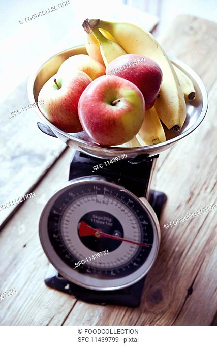 Apples and bananas on a pair of kitchen scales