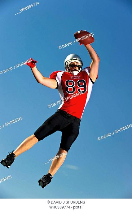 American Football player jumps high to make the catch