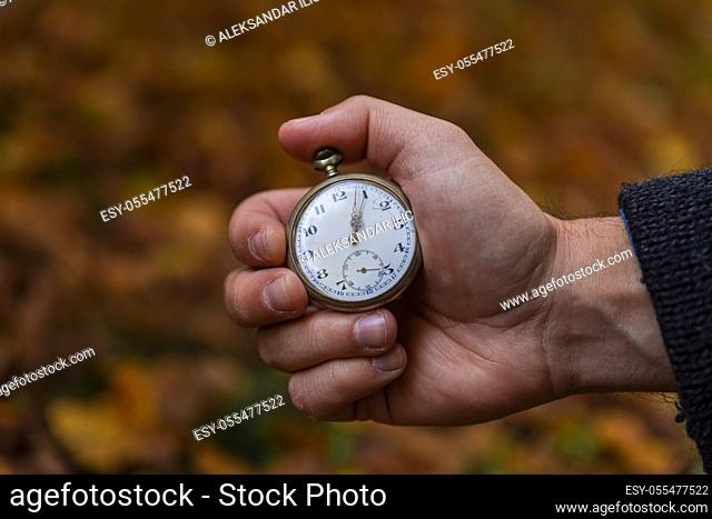 Vintage Pocket watch in man's hand against the background of autumn dried brown leaves