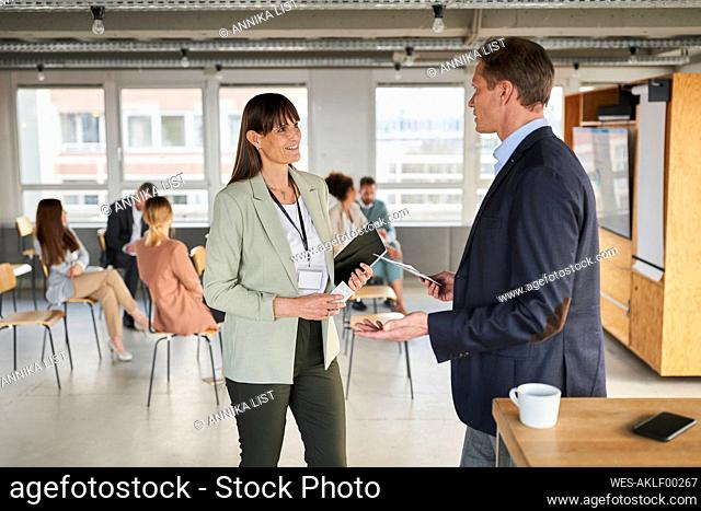 Businesswoman discussing with colleague at education even in office