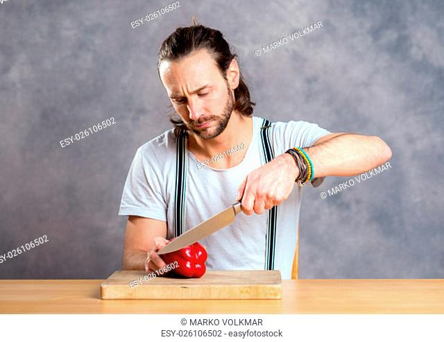 young bearded man cutting sweet pepper in front of gray background