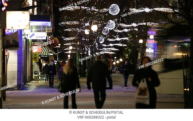 People are rushing though a pedestrian zone at Christmas time. Fairy lights are glittering over the street. Busses are crossing the pedestrian precinct