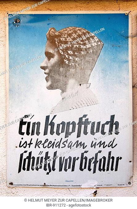 Ein Kopftuch ist kleidsam und schuetzt vor Gefahr, or a headscarf is becoming and protects from danger, a warning sign of the Worker's Accident Prevention and...