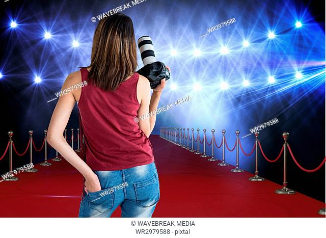Woman from behind on a red carpet with camera on her hands