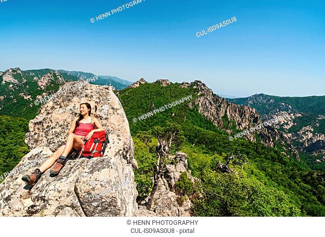 Female hiker relaxing on rock formation on way to Daecheongbong peak, Seoraksan National Park in South Korea