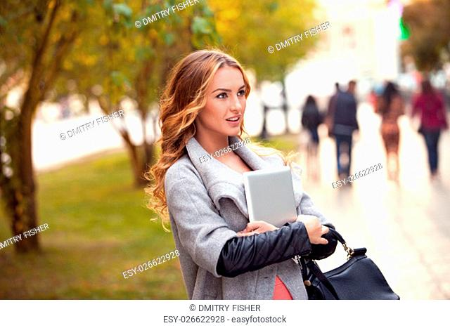 A businesswoman with a tablet walking in a city park