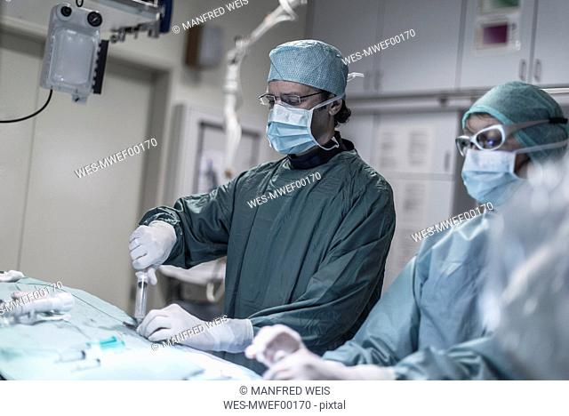 Neuroradiologist with assistant using syringe during an operation
