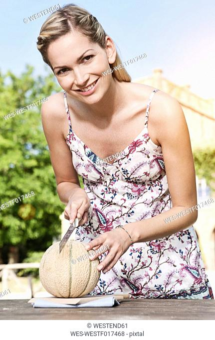 Italy, Tuscany, Magliano, Young woman cutting honey melon, smiling, portrait