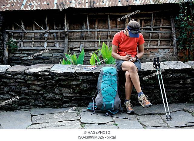 Woman stops for a break along stone-paved street, Ngadi, Nepal