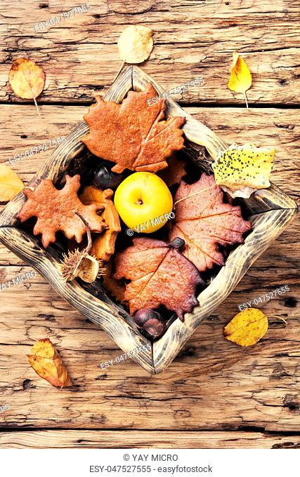 Autumn still life with cookies in the form of autumn leaves, apples and fallen leaves.Autumn concept