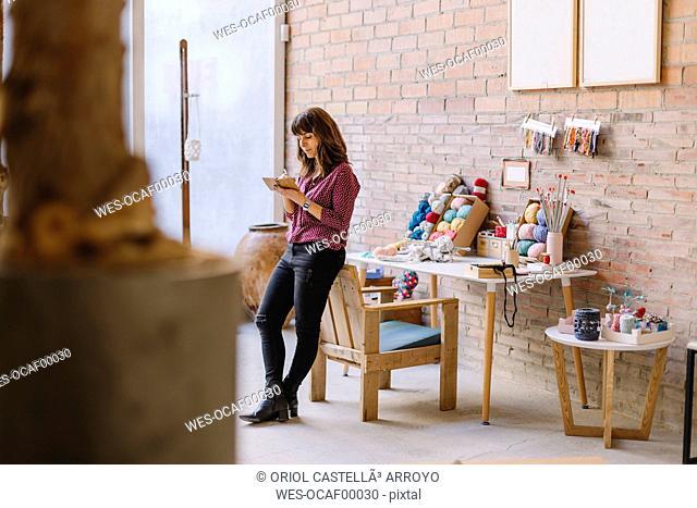 Woman in knitting studio taking notes