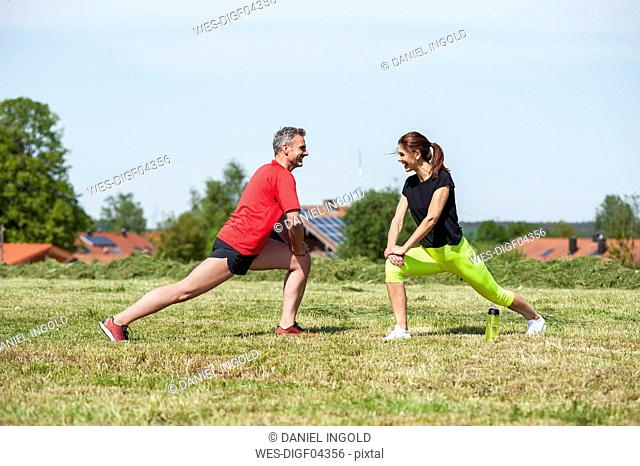 Couple doing stretching exercise on meadow