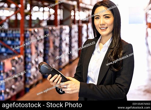 Portrait of businesswoman hold credit card reader in large factory and distribution warehouse environment. Business deal merger acquisitions and takeover