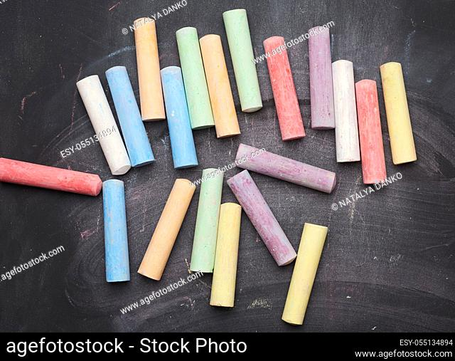 multicolored chalks on lie on empty black chalk board, top view, back to school