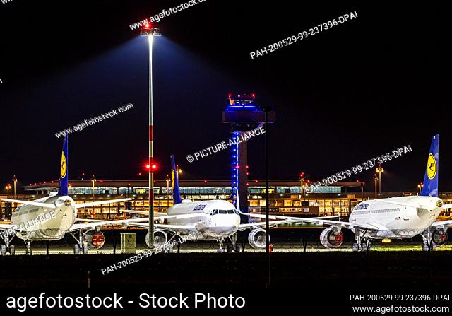 29 May 2020, Brandenburg, Schšönefeld: Lufthansa planes stand behind a fence behind Terminal 1 of the capital's Willy Brandt airport