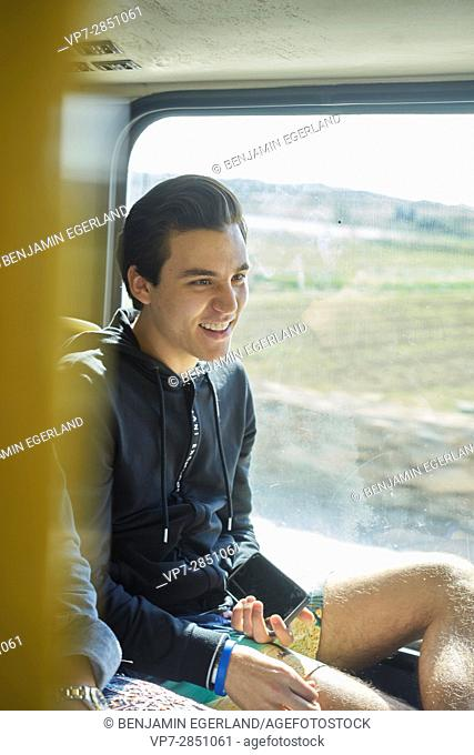exhilarated young man is sitting in public transport and laughing