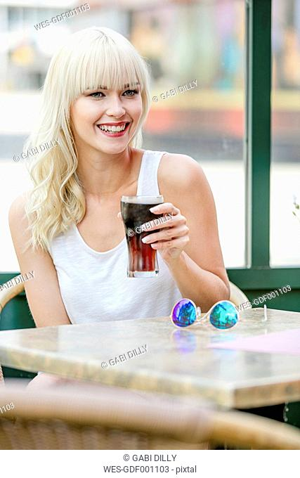 Portrait of smiling blond woman sitting at sidewalk cafe drinking cola