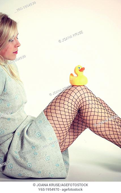 a blond girl with a turqouise dress is sitting with a rubber duck on her knees