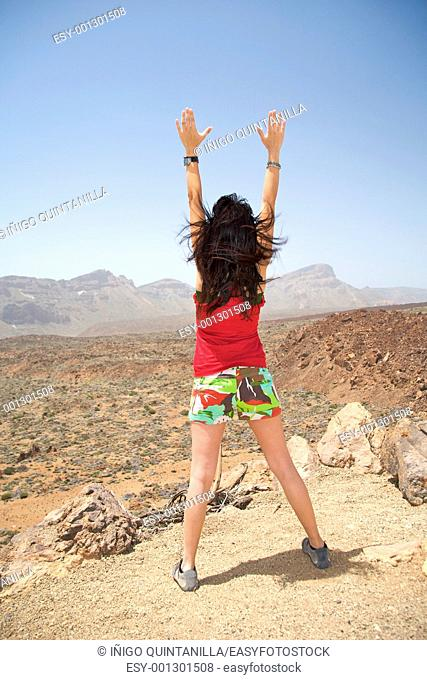 woman opening arms near the teide volcano in tenerife spain