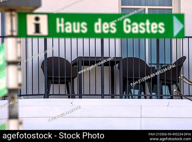"""06 May 2021, Mecklenburg-Western Pomerania, Bansin: An empty holiday balcony of a beach hotel can be seen behind the signpost to the """"""""Haus des Gastes"""""""""""