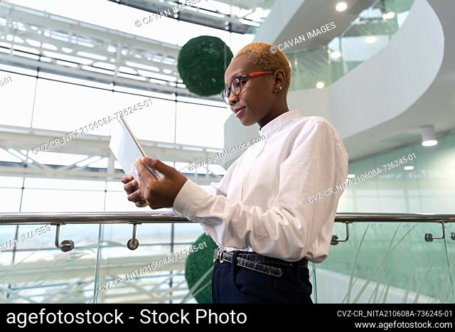 African American analyst browsing tablet near railing