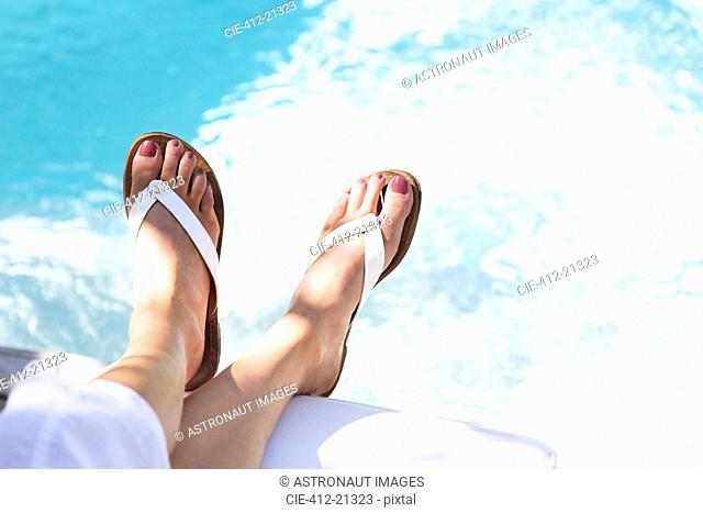 Close up of woman's feet dangling over swimming pool