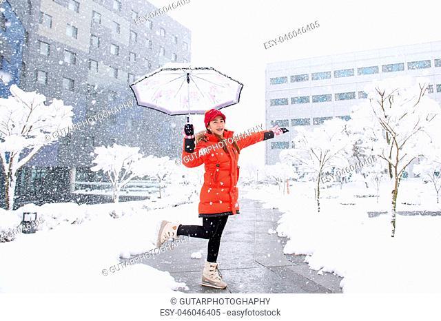 Snow falling on beautiful girl with umbrella in winter