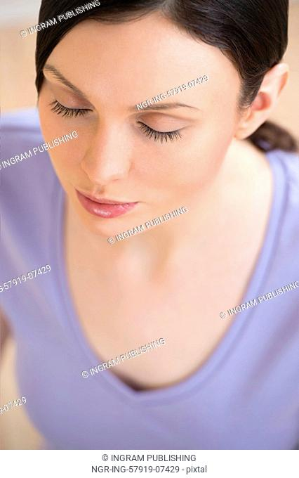 Portrait of beautiful young woman doing yoga exercise - Meditating