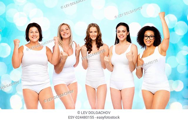success, friendship, beauty, body positive and people concept - group of happy plus size women in white underwear celebrating victory over blue holidays lights...